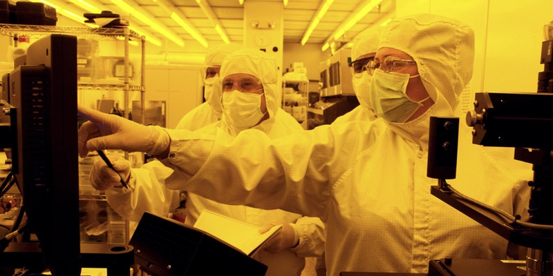 Faculty conduct research in a lab with clean suits on.