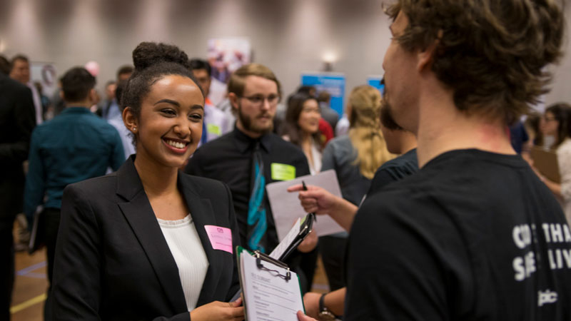 A smiling student talks with a recruiter at Career Fair