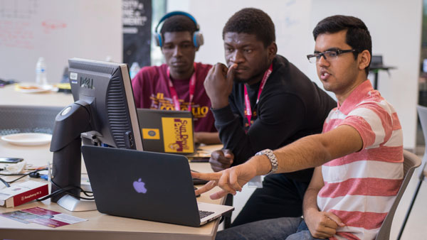 Three students collaborate on a laptop.